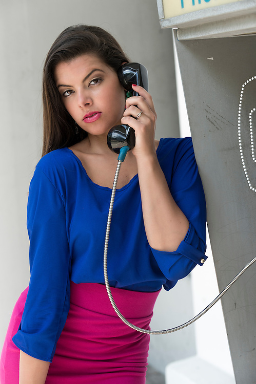 Young woman talking in a public phone.