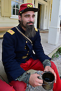"""Old Bethpage, New York, USA. 30th August, 2015. ANDREW PREBLE from Long Beach portrays an American Civil War soldier Captain from the 14th Brooklyn Regiment (14th New York State Militia) AKA The Brooklyn Chasseurs, at the Noon Inn tavern during the Old Time Music Weekend at the Old Bethpage Village Restoration. During their historical reenactments, members of the non-profit 14th Brooklyn Company E wear accurate reproductions of """"The """"Red Legged Devils"""" original Union army uniform."""