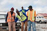 Constructiewerkers poseren. Veel contractwerkers zijn jong en student, en doen dit werk als tijdelijke zomerbaan.