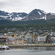 The town of Ushuaia hugging the waterfront, with steep, snowy mountains in the background.