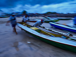 August 3, 2017 - Kuta, Bali, Indonesia - Villagers push their outrigger canoes into the surf before sunrise along Jimbrana Beach in Kuta. The beach is close to the airport and a short drive from other beaches in southeast Bali. Jimbrana was originally a fishing village with a busy local market. About 25 years ago, developers started building restaurants and hotels along the beach and land prices are rising. The new emphasis on tourism is changing the nature of the area but the fishermen are still busy very early in the morning. (Credit Image: © Jack Kurtz via ZUMA Wire)