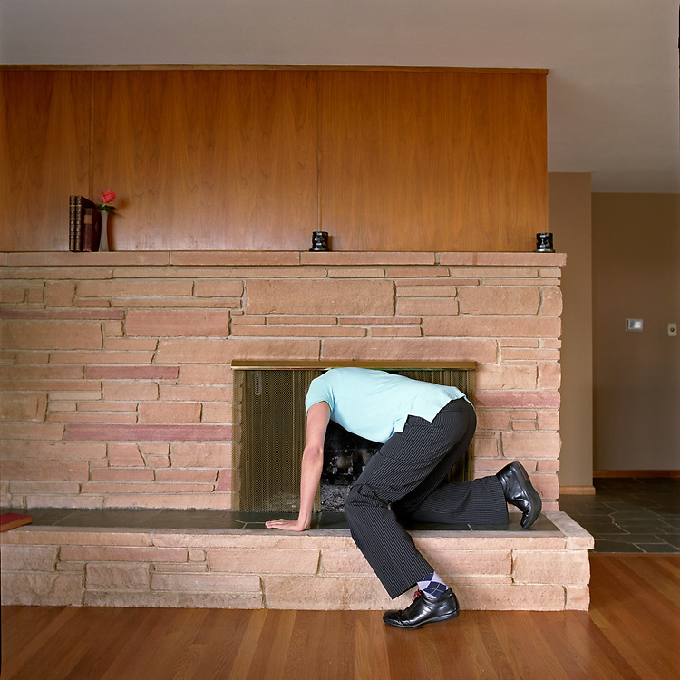 Young man sticking head in residential fireplace.