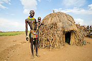 Young Nyangatom woman with baby in arms, stands next to her thatch hut. Omo Valley, Ethiopia
