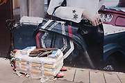An advertising image juxtaposed with bags of cement building materials on the ground in Bond Street, central London. Looking at the lower left corner of the advertising space on this street, we see the prosperity of the models arm that carries an exclusive bag by Italian Tods brand who make a unique style of shoes, bags and accessories. Still on its trolley and awaiting use on the construction site behind the hoarding, the cement is bagged up in afternoon sunshine.