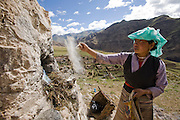 A woman performs a religious ritual outside a Buddhist monastery in the Tibetan Plateau.