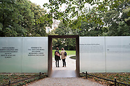 Berlin, Germany - September 3, 2015: Two women stand just inside the entrance to the Memorial to the Sinti and Roma Victims of National Socialism. Designed by Dani Karavan, it was officially opened by Chancellor Angela Merkel on October 24, 2012. It is dedicated to the memory of the 220,000 - 500,000 people murdered by the Nazis in the Porajmos, the genocide of the European Sinti and Roma peoples.
