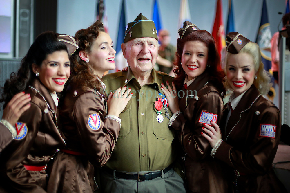 06 June 2014. The National WWII Museum, New Orleans, Lousiana. <br /> WWII veteran Pfc Horace Calhoun, Company K, 116th Infantry, 3rd Battalion is honored with the French Legion of Honor medal. Surrounded here by the 'Victory Belles.' <br /> Photo; Charlie Varley/varleypix.com