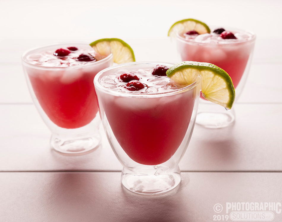 Colored natural cranberry drinks with lime slices