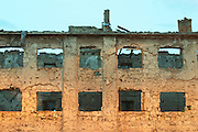 Building in Mostar damaged by the war and still not renovated. Ruined by bullet holes, mortar bomb shell grenade damage, very close to the beautifully renovated old town city centre. Along a busy main street in evening light with yellow street light giving an eerie atmosphere. Detail. Town of Mostar. Federation Bosne i Hercegovine. Bosnia Herzegovina, Europe.