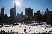 People ice skating around the Wollman Rink in the southern park of Central Park, Manhattan, New York City, New York, United States of America.  Snow surrounds the public ice rink.