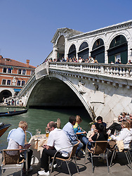 Tourists sitting in cafe beside famous Rialto Bridge in Venice Italy