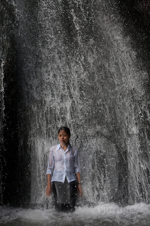 A young vietnamese girl bath in the Silver waterfall of Tam Dao, Vietnam, Asia