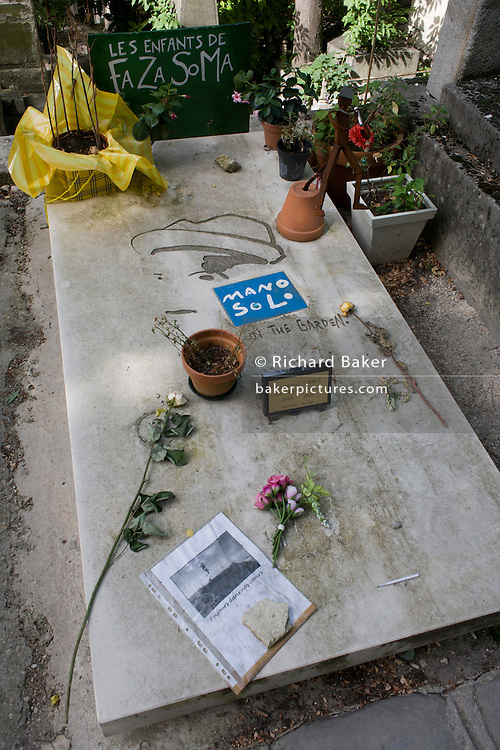 """Tomb of the punk singer and musician Mano Solo in the Pere Lachaise cemetery, Paris. Mano Solo (1963-2010), Mano Solo developed other talents, including art. He designed the covers of some of his albums. He founded his own publishing imprint (La Marmaille Nue), which released two of his own books: a poetry anthology, Je suis là (""""I am here"""") (1995), and a novel, Joseph sous la pluie (""""Joseph in the rain"""") (1996). From 2001, Solo became interested in the Internet creating his own website around his artistic, social, and political interests, while encouraging his visitors to be creative themselves..Solo, who suffered from HIV/AIDS, was rushed to a hospital after a concert in Paris."""