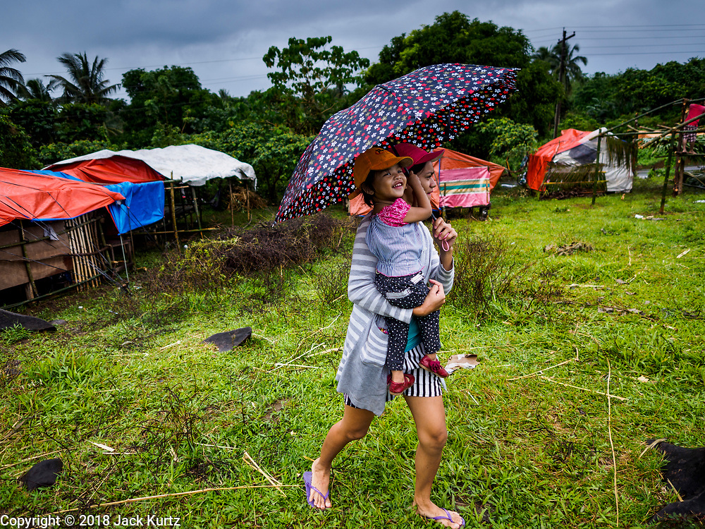 26 JANUARY 2018 - SANTO DOMINGO, ALBAY, PHILIPPINES: A woman and her child, both evacuated from the home on the slopes of the Mayon volcano, walk through field where they've built their temporary shelter. The volcano was relatively quiet Friday, but the number of evacuees swelled to nearly 80,000 as people left the side of  the volcano in search of safety. There are nearly 12,000 evacuees in Santo Domingo, one of the communities most impacted by the volcano. The number of evacuees is impacting the availability of shelter space. Many people in Santo Domingo, on the north side of the volcano, are sleeping in huts made from bamboo and plastic sheeting. The Philippines is now preparing to house the volcano evacuees for up to three months.     PHOTO BY JACK KURTZ