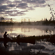 Canoiest and dog fishing from canoe on small lake. Early morning. Northern Minnesota.