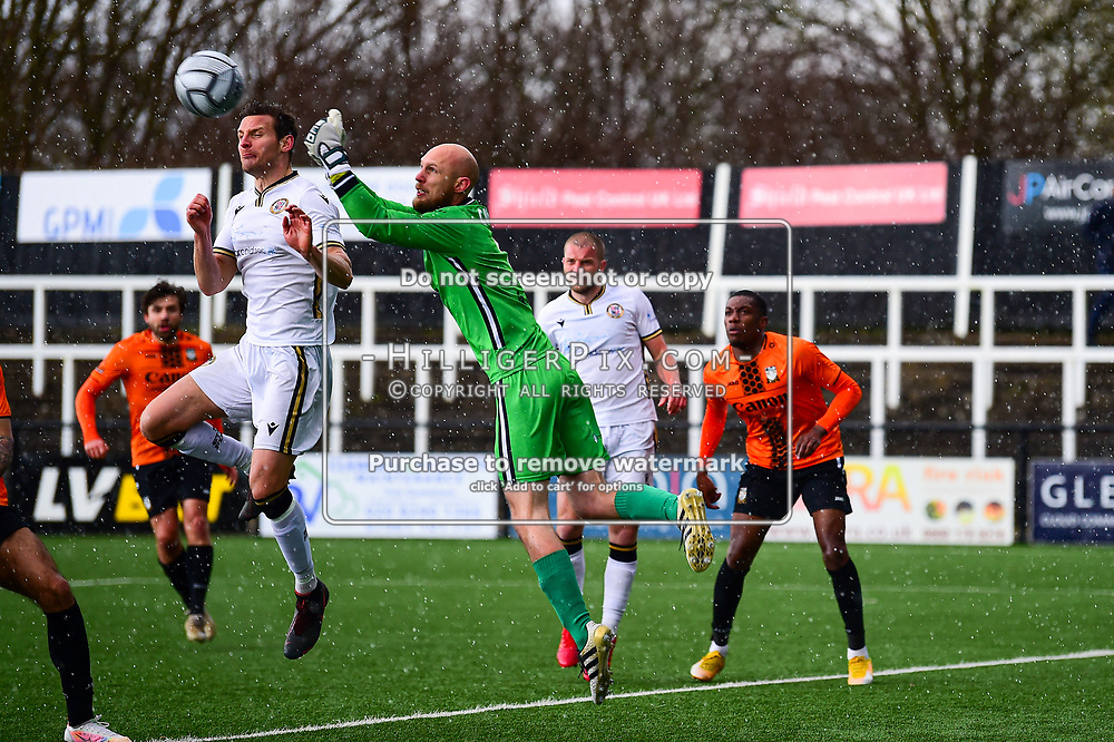 Bromley   England    13 March 2021   Westminster Waste Stadium<br /> <br /> Bromley's Jack Holland rises for a defensive header as his goalkeeper  Mark Cousins comes out to push the ball clear<br /> <br /> Bromley v Barnet<br /> <br /> Vanarama National League<br /> <br /> (Photo: © Jon Hilliger / HilligerPix)