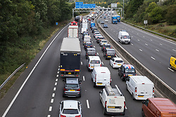 Godstone, UK. 13th September, 2021. Traffic is queued on the M25 after climate activists from Insulate Britain blocked a slip road as part of a new campaign intended to push the UK government to make significant legislative change to start lowering emissions. The activists, who wrote to Prime Minister Boris Johnson on 13th August, are demanding that the government immediately promises both to fully fund and ensure the insulation of all social housing in Britain by 2025 and to produce within four months a legally binding national plan to fully fund and ensure the full low-energy and low-carbon whole-house retrofit, with no externalised costs, of all homes in Britain by 2030 as part of a just transition to full decarbonisation of all parts of society and the economy.