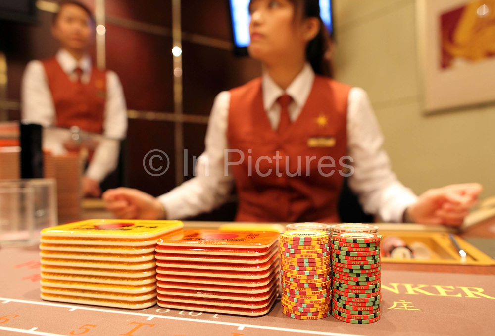 A casino dealer arranges chips at the Galaxy's Starworld Casino in Macau, China on 27 January 2011. A relative newcomer to the rapidly expanding Macau gambling scene, the Galaxy hopes its new casino will hold up its own against the likes of the Venetian, Wynn, MGM, and the Lisboa.