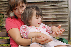 Young girl with autism sitting on mother's lap stroking her hands,