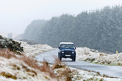 © Licensed to London News Pictures. 12/01/2017. Builth Wells, Powys, Wales, UK. A four wheel drive vehicle drives through a wintry landscape on the high moorland of the Mynydd Epynt range near Builth Wells in Powys, Mid Wales, UK. Photo credit: Graham M. Lawrence/LNP