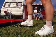 Seen from ground-level, a pair of feet in white trainers are seen large in the foreground on lush grass, one standing on a foot pump as it inflates a camping lilo air bed on a summer afternoon at the Trewethett Farm Caravan Club Site, Tintagel, Cornwall. Seen through the man's bare legs, the man's wife sits in front of the caravan's awning on a sun chair, cuddling the family pet dog. Caravanning is one the favourite leisure pastimes in Britain, its association, the elite Caravan Club, was founded in 1907 and now represents nearly 1 million members (caravanners, motor caravanners and trailer tenters) and has an  annual turnover of £86 million. On the open road, the caravan is as ridiculed and despised for its slowness and the width it occupies on narrow country lanes.
