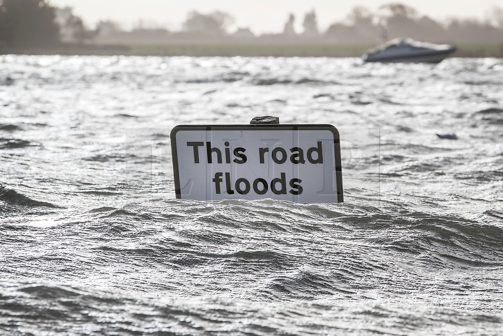 © Licensed to London News Pictures. 03/01/2018. Bosham, UK. A sign on a road swamped in tidal flood water warns drivers in Bosham as storm Eleanor hits the south. Winds of up to 80 mph are being forecast today in parts of the UK. Photo credit: Peter Macdiarmid/LNP