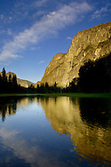 Golden sunrise light on rock cliffs over flooded meadow in spring, Yosemite Valley, Yosemite National Park, California