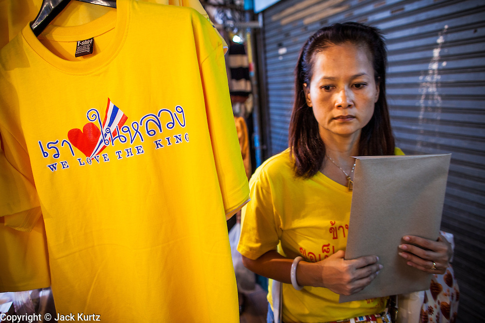 04 DECEMBER 2012 - BANGKOK, THAILAND:  A woman dressed in yellow walks past a booth in front of Siriraj Hospital selling yellow tee shirts honoring Bhumibol Adulyadej, the King of Thailand. Yellow is the official color of the Thai King, who celebrates his 85th birthday Wednesday, Dec. 5. The King lives in Siriraj. He is expected to make a rare public appearance and address the nation from Mukkhadej balcony of the Ananta Samakhom Throne Hall in the Royal Plaza. The last time he did so was in 2006. His birthday is a public holiday in Thailand and hundreds of thousands of people are expected to jam the streets around the Royal Plaza and Grand Palace to participate in the festivities.   PHOTO BY JACK KURTZ