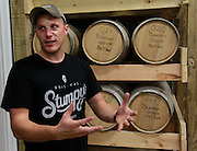 Adam Stumpf with barrels of bourbon that have been produced at Stumpy's Distillery in rural Columbia.