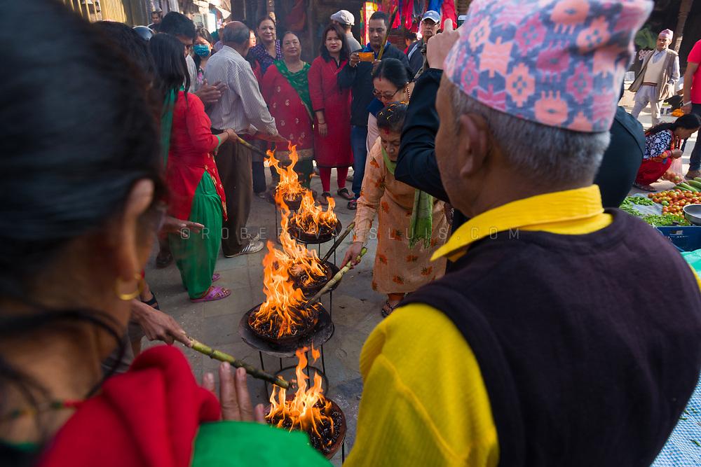 A family performing a fire ritual at Durbar Square, Nepal. Photo © robertvansluis.com