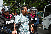 07 AUGUST 2013 - BANGKOK, THAILAND: Thai riot police arrest anti-amnesty, anti-government protesters in Bangkok. About 2,500 protestors opposed to an amnesty bill proposed by Thailand's ruling party marched towards the Thai parliament in the morning. The amnesty could allow exiled fugitive former Prime Minister Thaksin Shinawatra to return to Thailand. Thaksin's supporters are in favor of the bill but Thai Yellow Shirts and government opponents are against the bill. Thai police deployed about more than 10,000 riot police and closed roads around the parliament. Although protest leaders called off the protest rather than confront police, a few people were arrested for assaulting police when they tried to break through police lines. Several police officers left the scene under medical care after they collapsed in the heat.    PHOTO BY JACK KURTZ