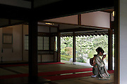 young woman in kimono sitting and drinking tea in a traditional Japanese house with garden