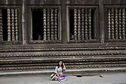 An Asian woman sits and rests besides beautiful stone carvings decorating a walkway within a gallery in Angkor Wat temple complex Siem Reap, Cambodia.  Angkor Wat is one of UNESCO's world heritage sites. It was built in the 12th century and covers 162 hectares.  It is Cambodia's main tourist attraction.