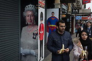 A family of Middle-eastern appearance visiting the capital, walk past the images of Queen Elizabeth II, a guardsman and Superman, on 3rd February 2017, in London, England.