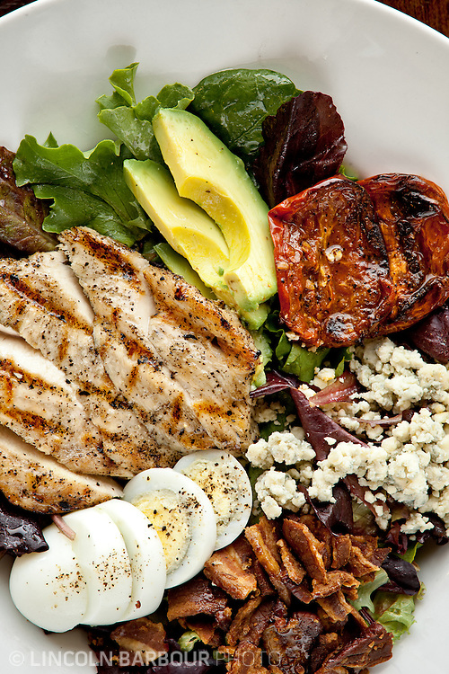 A close up of a cobb salad loaded with food including, hard boiled egg, chicken, bacon, avocado, etc.