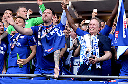 Cardiff City manager Neil Warnock (right) and the Cardiff City players celebrate winning their promotion to the Premier League after the Sky Bet Championship match at the Cardiff City Stadium.