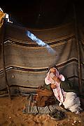 A Bedouin man smokes a cigarette in his remote home encampment in Wadi Rum, Jordan.