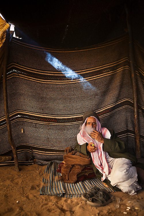 A Bedouin man smokes a cigarette in his remote home encampment in Wadi Rum, Jordan.