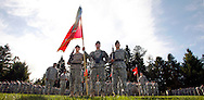 Spc. Sean Curtis, Anniston, Ala. to the left of flag, Spc. Ronald Bowling, Beckley, W. Wa., center holding flag, and Spc. Andres Gomez, Miami. stand in front of of other soldiers in the Army 4th Brigade, 2nd Infantry Division Stryker Brigade at a deployment ceremony at Fort Lewis, WA. (AP Photo/John Froschauer)