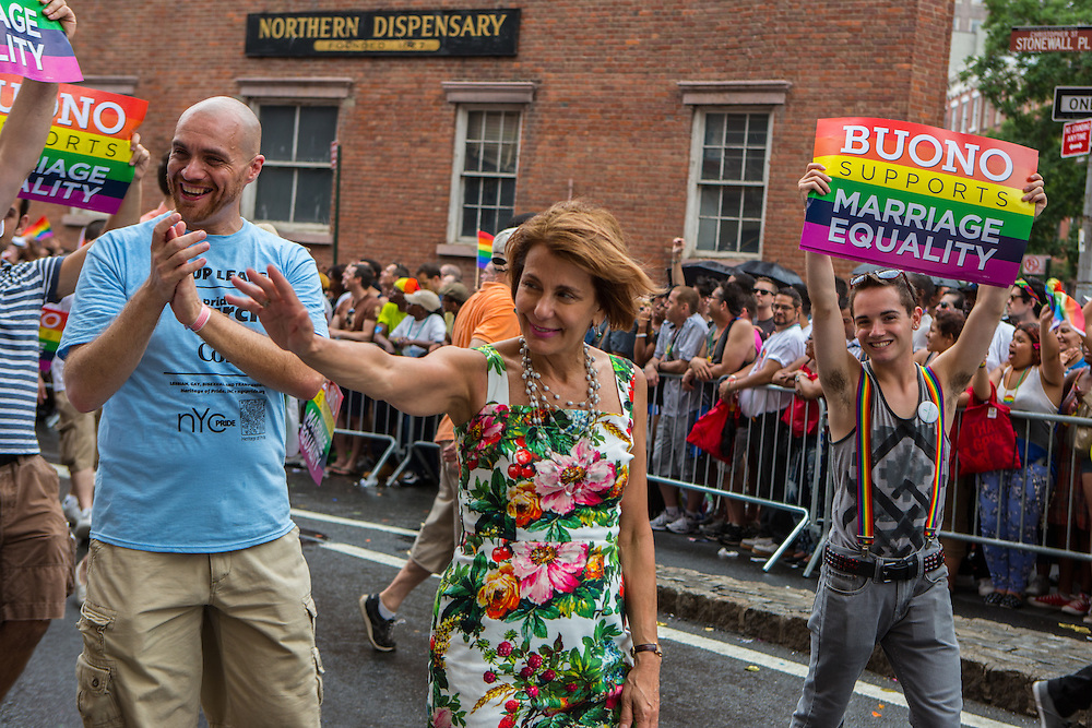 """New York State Senator Barbara Buono waves to the crowd on Chirstopher Street. A member of her entourage carries sign that reads """"Buono suports marriage equality."""""""