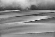 Storm clouds and fog rolling in on the large sand dunes of the Skeleton Coast, black and white, Namibia