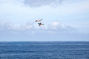 Person flying microlight plane over the ocean, Caleta de Caballo, Lanzarote, Canary islands, Spain