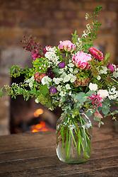 Arrangement of spring flowers in a large glass jam jar