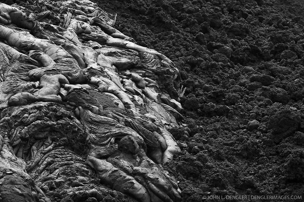 Pahoehoe lava (right) has a smooth surface where as `a`a lava has a rough surface. In an eruption where a lot of lava is being discharged at once - `a`a flows tend to form. If the rate is low, a pahoehoe flow is more likely. This example from Hawaii Volcanoes National Park on the Big Island of Hawaii shows both types of lava.