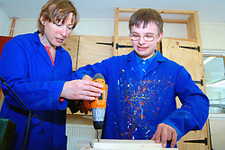 Young man with Downs Syndrome learning how to use a drill at a workshop for craftspeople with learning disabilities UK
