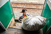 15 JUNE 2013 - YANGON, MYANMAR:  A woman gets off the Yangon Circular Train with a bag of vegetables she hopes to sell. Yangon Circular Railway is the local commuter rail network that serves the Yangon metropolitan area. Operated by Myanmar Railways, the 45.9-kilometre (28.5mi) 39-station loop system connects satellite towns and suburban areas to the city. The railway has about 200 coaches, runs 20 times and sells 100,000 to 150,000 tickets daily. The loop, which takes about three hours to complete, is a popular for tourists to see a cross section of life in Yangon. The trains from 3:45 am to 10:15 pm daily. The cost of a ticket for a distance of 15 miles is ten kyats (~nine US cents), and that for over 15 miles is twenty kyats (~18 US cents). Foreigners pay 1 USD (Kyat not accepted), regardless of the length of the journey.     PHOTO BY JACK KURTZ