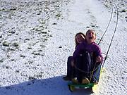 Two young girls screaming as their snow sledge races down a steep hillside, Burrow Hill, Boyton, Suffolk, England, Uk