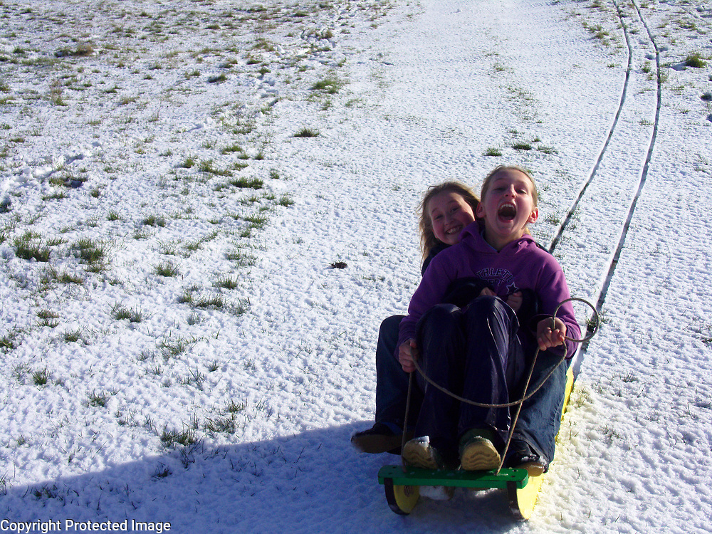 Two young girls screaming as their snow sledge races down a steep hillside, Burrow Hill, Boyton, Suffolk, England, Uk