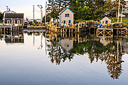 The lobster docks and piers piled high with traps in the quaint fishing harbor of Port Clyde, Maine.