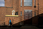 A local shopper walks beneath an effigy of Jesus Christ encased in a shrine box outside a Catholic church in Camberwell, south London. Encased in a glass-sided box and behind what resembles yellow garden fencing, the Christian idol stands with outstretched arms, a traditional figure for Catholics to practice idolatry. The church walls are constructed from red brick, in a style much-seen in industrial buildings.